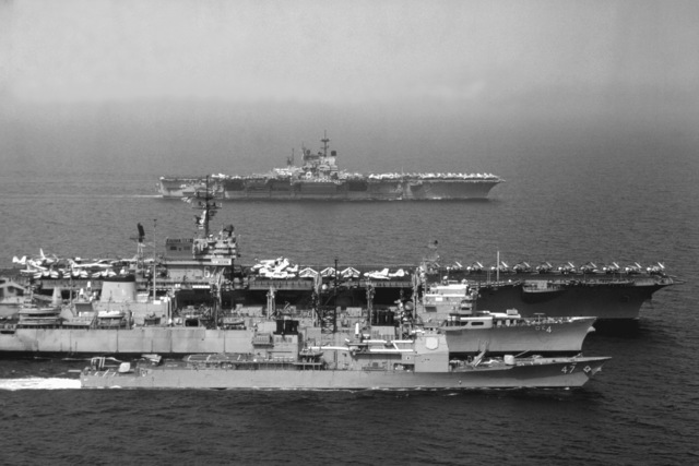 Aerial starboard beam view of, front to back, the guided missile cruiser USS TICONDEROGA (CG-47), the fast combat ship USS DETROIT (AOE-4), the aircraft carrier USS JOHN F. KENNEDY (CV-67) and the aircraft carrier USS INDEPENDENCE (CV-62) underway