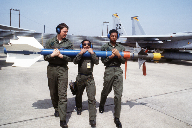 AIRMAN First Class (A1C) James R. Nichols, left, Sergeant (SGT) Ricky Brown, center, and SENIOR AIRMAN (SRA) Victor Allen, right, carry an AIM-9 Sidewinder missile away from an F-15 Eagle aircraft during Exercise TEAM SPIRIT '84. They are aircraft arament specialists with the 18th Aircraft Generation Squadron