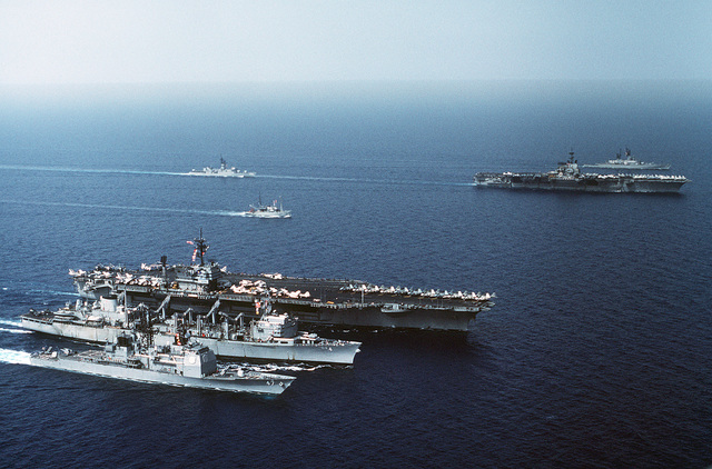 An aerial starboard view of, front to back, left side: the guided missile cruiser USS TICONDEROGA (CG-47), the fast combat ship USS DETROIT (AOE-4), the aircraft carrier USS JOHN F. KENNEDY (CV-67), the salvage ship USS HOIST (ARS-40) and a Knox Class frigate. Right side is the aircraft carrier USS INDEPENDENCE (CV-62) and a Leahy Class guided missile cruiser