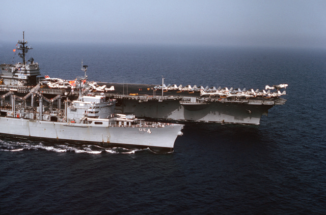An elevated starboard bow view of the aircraft carrier USS JOHN F. KENNEDY (CV 67) underway off the coast of Lebanon. An A-6 Intruder aircraft has just been launched from the flight deck. The fast combat support ship USS DETROIT (AOE 4) is alongside the carrier