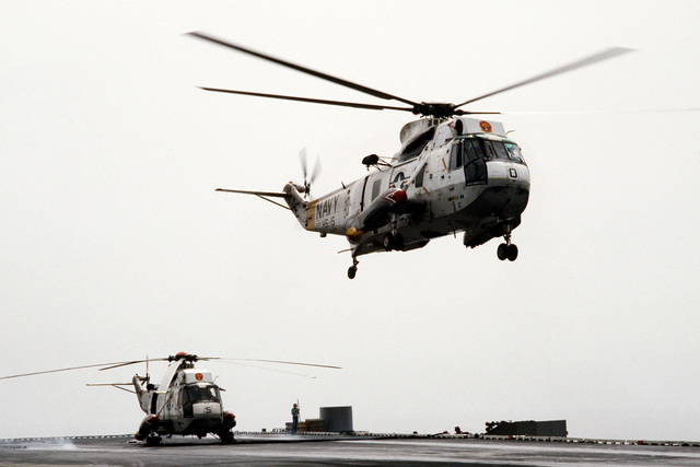 An SH-3H Sea King helicopter from Helicopter Anti-Submarine Squadron 15 lifts off from the aircraft carrier USS JOHN F. KENNEDY (CV 67) during operations off the coast of Lebanon. Another SH-3H from the same squadron is parked on the flight deck. The helicopters are assigned to the aircraft carrier USS INDEPENDENCE (CV 62)