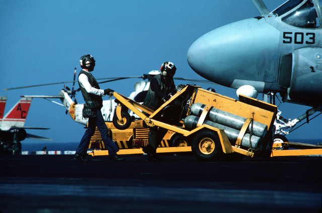 Flight deck crewmen transport an NAN-2 nitrogen servicing unit across the flight deck of the aircraft carrier USS JOHN F. KENNEDY (CV 67) during operations off the coast of Lebanon. The nose section of an A-6E Intruder aircraft is visible on the right