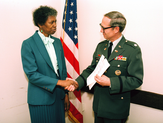 Lieutenant Colonel (LTC) James T. Van Orden Jr., right, commanding officer, US Army Audiovisual Center (USAAVC), presents a copy of the union contract between USAAVC and the American Federation of Government Employees (AFGE) Local 2 to Mildred S. Moseley, president, AFGE Local 2, during a contract signing ceremony at the Pentagon