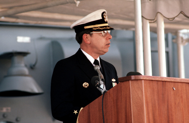 An officer addresses guests attending the commissioning ceremony for the Oliver Hazard Perry-class guided missile frigate USS NICHOLAS (FFG 47) at the Bath Iron Works shipyard