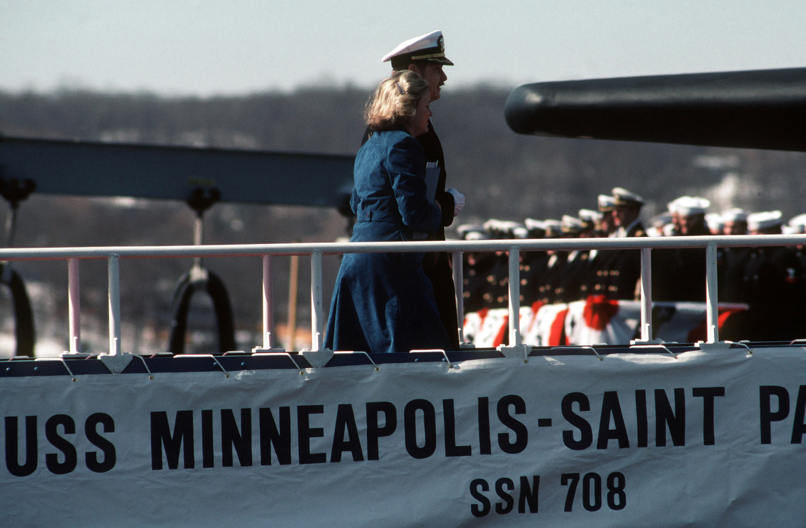 Mrs. David Durenberger, Sponsor, is escorted aboard the nuclear-powered attack submarine USS MINNEAPOLIS-ST. PAUL (SSN 708) during the ship's commissioning ceremony at General Dynamics (Electric Boat)