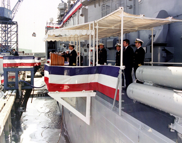 Naval officers and other distinguished guests stand on the speakers platform during the commissioning of the guided missile frigate NICHOLAS (FFG-47)