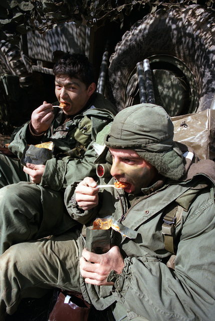PVT. Stephen Argenzio and SPEC. 4 Joe Chavez of Combat Support Company, 1ST Bn., 14th Inf., 25th Inf. Div., eat Meal-Ready-to-Eat (MRE) rations during the joint South Korean/U.S. training Exercise Team Spirit '84