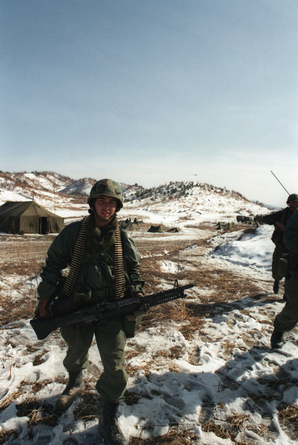 A member of Company B, 1ST Battalion, 21st Infantry, 25th Infantry Division, participates in a live-fire training near Chunchon during the joint South Korean/US training Exercise TEAM SPIRIT '84. He is armed with an M60 machine gun and is carrying 7.62 mm ammunition for the gun