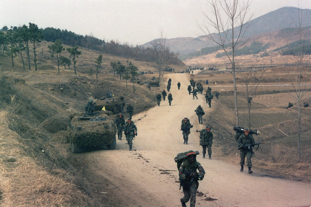 Members of Company B, 1ST Battalion, 21st Infantry, 25th Infantry Division, participate in live-fire training near Chunchon during the joint South Korean/US training Exercise TEAM SPIRIT '84. The soldier in the foreground is armed with an M203 grenade launcher mounted on an M16A1 rifle