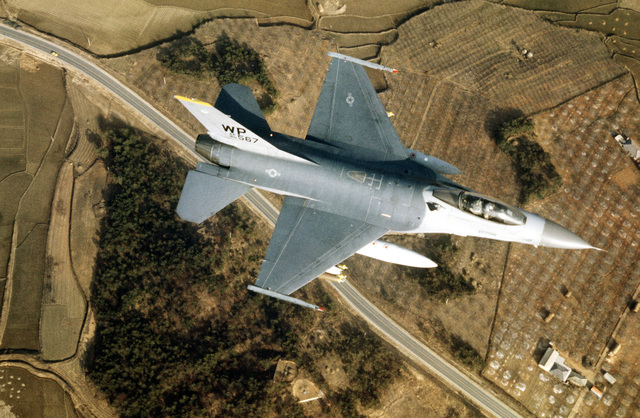 An air-to-air overhead view of an 80th Tactical Fighter Squadron F-16 Fighting Falcon aircraft approaching Chik-Tow range during the joint US/South Korean Exercise TEAM SPIRIT '84. The F-16 is armed with Mark 82 bombs