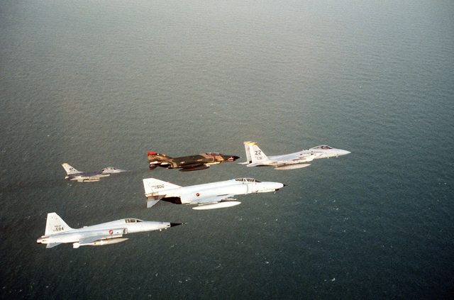 An air-to-air right side view of a Korean Air Force F-5 Tiger II aircraft and F-4 Phantom II aircraft in formation with a US Air Force F-16 Fighting Falcon, F-4 Phanton II aircraft, and F-15 Eagle aircraft during the joint US/South Korean Exercise TEAM SPIRIT `84