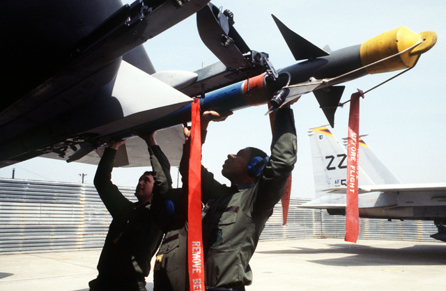 Armament specialists from the 18th Aircraft Generation Squadron load a Sidewinder (AIM-9) missile onto the wing pylon of an F-15 Eagle aircraft during the joint US/ Korean Exercise TEAM SPIRIT '84