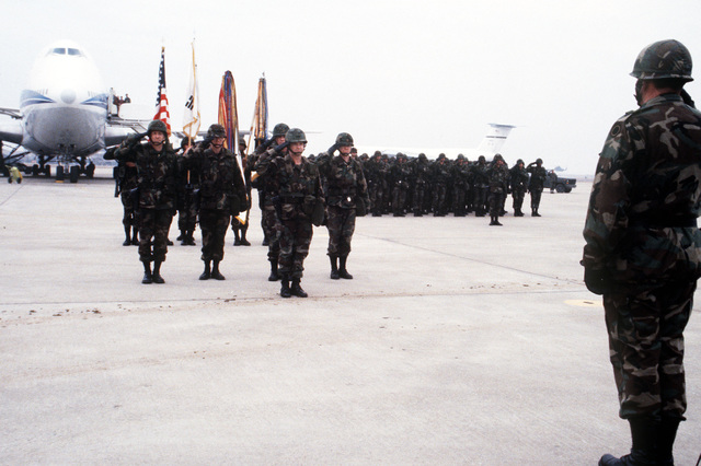 Lieutenant General John Brandenburg returns a salute to soldiers standing in formation. The men have just arrived aboard a Boeing 747 to participate in exercise TEAM SPIRIT '84