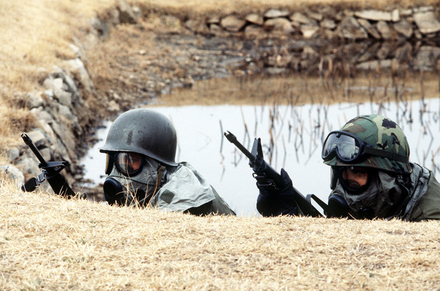Members of the 51st Security Police Squadron wear nuclear, biological, and chemical (NBC) gear during a hostage exercise. They are participating in the joint US/South Korean Exercise TEAM SPIRIT '84