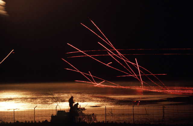 Tracer rounds light up the sky as a nighttime live-fire exercise takes place during the joint US/South Korean Exercise TEAM SPIRIT '84. Members of the 8th Security Police Squadron Air Base Ground Defense Team man an armored personnel carrier in the foregr
