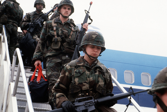 U.S. soldiers exit a Boeing 747 aircraft upon their arrival to participate in exercise Team Spirit '84. The soldiers are carrying M-16A1 rifles