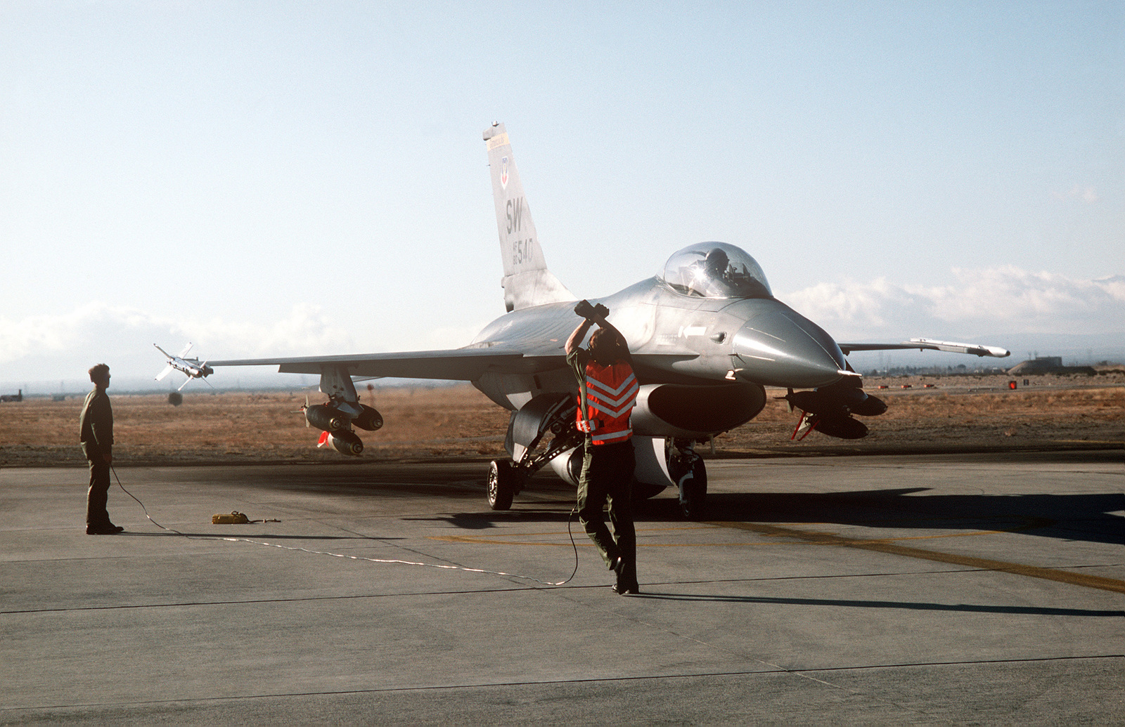 A ground crewman signals the pilot of an F-16 Fighting
