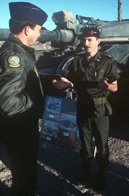"Army First Lieutenant Steve Rundle briefs an Air Force pilot on the converted Sheridan tanks being used during Exercise AIR WARRIOR. He explains that with some modification using fiberglass, the tanks can be made to look like ""enemy"" armored vehicles"