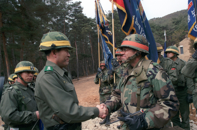 Lieutenant General Kim Dong Chun, left, commander, III Corps, South Korean army, shakes hands with Colonel David E.K. Cooper, commanding officer, 2nd Brigade, 25th Infantry Division, during the Exercise TEAM SPIRIT '84 Operational Control ceremony