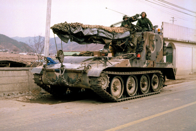 An M578 armored recovery vehicle armed with a .50-caliber machine gun travels down a road during Exercise TEAM SPIRIT 84
