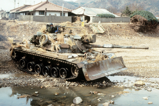 An M60 main battle tank, equipped with a bulldozer blade, prepares to cross a stream during Exercise TEAM SPIRIT 84
