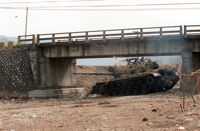 An M-48A5 main battle tank, with a bulldozer blade on the front, is set up under a bridge during the joint South Korea/US Exercise Team Spirit '84