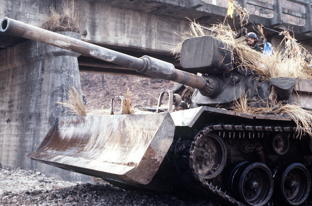 An M60 main battle tank, equipped with a bulldozer blade, sets up a defensive position in a stream bed during exercise TEAM SPIRIT '84