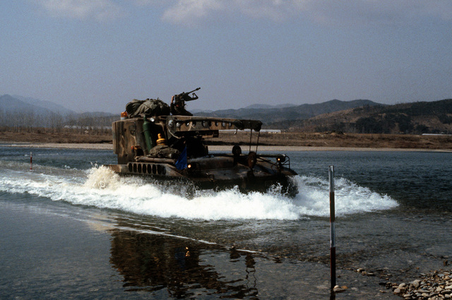 An M578 light armored recovery vehicle crosses a stream during Exercise TEAM SPIRIT 84