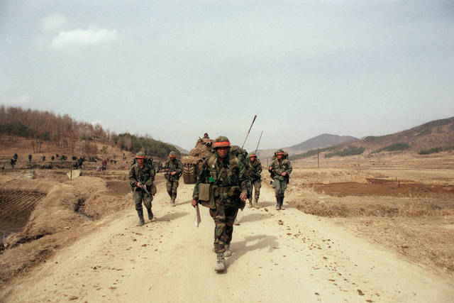 Lieutenant Colonel (LTC) Gene Bryson, commander, 1ST Battalion, 35th Infantry, 2nd Battalion, 25th Infantry Division, leads his troops down a dirt road supported by a South Korean army M47 tank, background, during the joint South Korean/US training Exercise TEAM SPIRIT '84