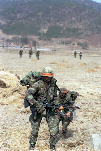 Members of the 2nd Battalion, 25th Infantry Division, move toward the Han River in an offensive against the Blue Forces during the joint South Korean/US training Exercise TEAM SPIRIT '84. They are acting as members of the Orange Forces
