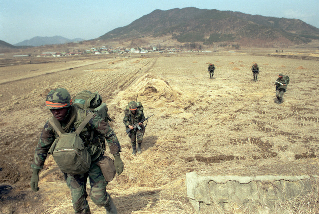 Members of the 2nd Battalion, 25th Infantry Division (Orange Forces), move toward the Han River in an offensive against the Blue Forces during the joint South Korean/US training Exercise TEAM SPIRIT '84