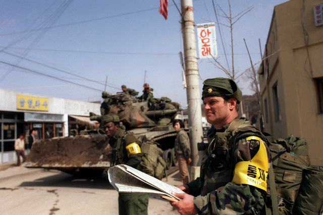 Major (MAJ) Edward R. Cruickshank, Commander of the 1ST Battalion, 299th Infantry, Hawaii Army National Guard, observes the entry of 25th Infantry Division Orange Forces into the city, as they advance against the Blue Forces during the joint South Korean/US Exercise TEAM SPIRIT '84. Visible to the left is an M728 combat engineer vehicle
