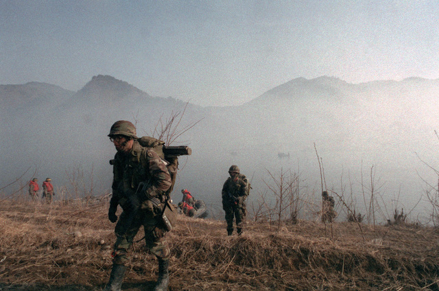 Members of the 2nd Battalion, 25th Infantry Division, (Orange Forces), come ashore on the northern bank of the Han River in an offensive against the Blue Forces during the joint South Korean/US training Exercise TEAM SPIRIT '84