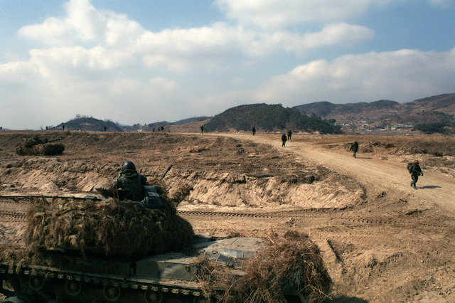 An M48 main battle tank of the South Korean army is used to cover members of the 2nd Brigade, 25th Infantry Division (Orange Forces), ash they march up a dirt road after crossing the river. They are involved in a battle with the Blue Forces during the joint South Korean/US Exercise TEAM SPIRIT '84