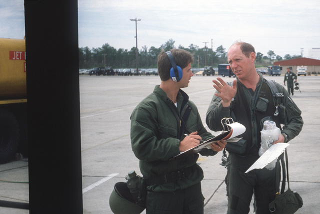 Colonel Tom Barber (right), director of operations, 33rd Tactical Fighter Wing (33rd TFW) is debriefed by First Lieutenant Robert M. Haire (left), intelligence officer, 33rd TFW