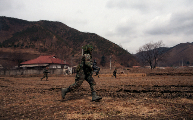 Members of Company A, 1ST Battalion, 14th Infantry, 25th Infantry Division, advance against the Blue Forces during the joint South Korean/US Exercise TEAM SPIRIT '84. They are acting as the Orange Force