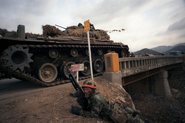 A member of Company A, 1ST Battalion, 14th Infantry, 25th Infantry Division, defends a bridge site with an M16A1 rifle during the joint South Korean/US Exercise TEAM SPIRIT '84. A South Korean army M48 main battle tank gives him protective cover