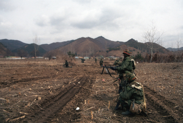 A member of Company A, 1ST Battalion, 14th Infantry, 25th Infantry Division, fires an M60 machine gun toward the Blue Forces during the joint South Korean/US Exercise TEAM SPIRIT '84. He is acting as a member of the Orange Forces