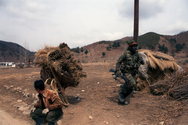 A member of Company A, 1ST Battalion, 14th Infantry, 25th Infantry Division, runs past a South Korean farmer as the Orange Forces battle the Blue Forces during the joint South Korean/US Exercise TEAM SPIRIT '84. The soldier is armed with an M16A1 rifle