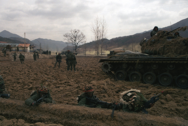 Members of Company A, 14th Infantry, 25th Infantry Division (Orange Forces), clash with Blue Forces along Highway 43 during the joint South Korean/US Exercise TEAM SPIRIT '84. The soldiers are armed, left to right, with an M16A1 rifle, an M60 machine gun and an M16A1 rifle equipped with an M203 grenade launcher. Behind them is an M48 tank