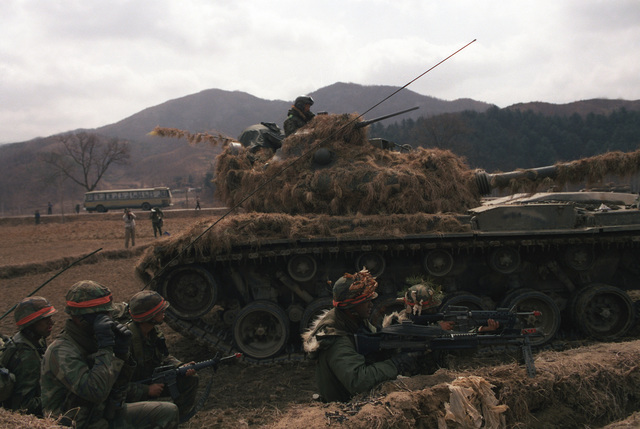 Members of Company A, 14th Infantry, 25th Infantry Division (Orange Forces), clash with Blue Forces along Highway 43 during the joint South Korean/US Exercise TEAM SPIRIT '84. The soldiers are armed, left to right, with an M16A1 rifle, an M60 machine gun and an M16A1 rifle equipped with an M203 grenade launcher. Behind them is an M-48 tank