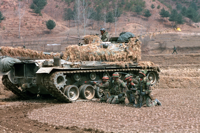 Members of Company A, 1ST Battalion, 14th Infantry, 25th Infantry Division (Orange Forces), battle Blue Forces along Highway 43 supported by a South Korean army M48 main battle tank, during the joint South Korean/US Exercise TEAM SPIRIT '84. The soldier next to the tank is firing an M16A1 rifle