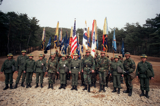 STAFF officers of the 25th Infantry Division and III Corps, South Korean army, stand in formation during Exercise TEAM SPIRIT '84 operational control ceremony. Lieutenant General Kim Dong Chun, commander, III Corps, South Korean army, and Major General William H. Schneider, commanding general, 25th Infantry Division, are in the center