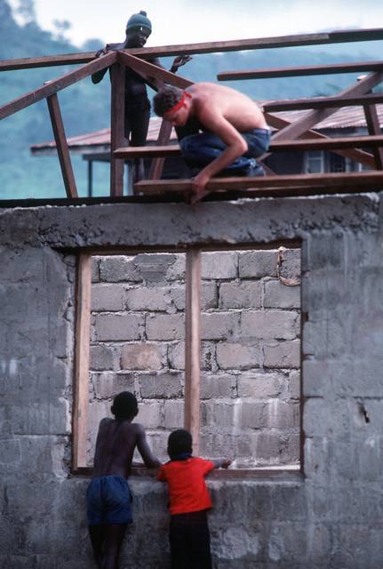 A crewman from the frigate USS JESSE L. BROWN (FF 1089) helps put a new roof on a school as some of the students give him a hand. Crewmen from the frigate are contributing American goods and know-how to the local residents as part of West African Training Cruise 1983. PHOTO from April 1984 All Hands Magazine