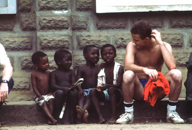 A crewman from the frigate USS JESSE L. BROWN (FF 1089) takes a break from building a school to talk to some children. PHOTO from April 1984 All Hands Magazine