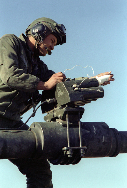 A member of 1/77 Armor loads a cartridge into a Hoffman gunfire simulator mounted on the barrel of his tank gun during a downrange training exercise