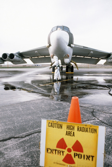 A member of the Strategic Air Command, wearing nuclear biological chemical (NBC) protective gear, sprays down the flight line in front of a B-52H Stratofortress aircraft as a decontamination exercise takes place during Exercise GLOBAL SHIELD '84