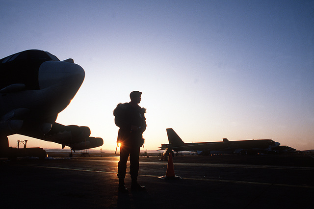A silhouetted view of AIRMAN 1ST Class William Haase guarding a B-52H Stratofortress aircraft on the flight line during Exercise Global Shield '84