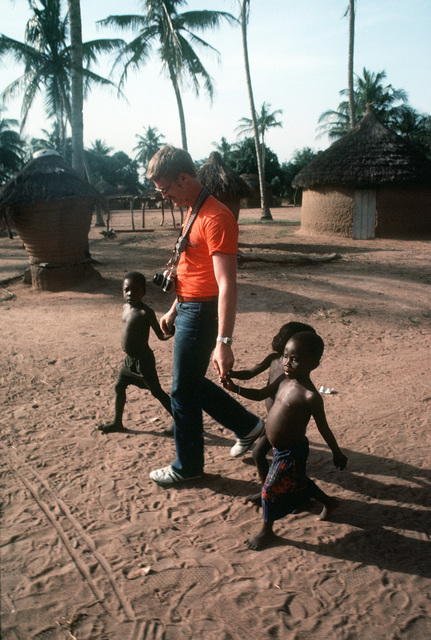 Boiler Technician 2nd Class (BT2) Paul Martin, a member of the American soccer team, gets a tour of the village from some of the native children. Martin is a participant in the West African Training Cruise. PHOTO from April 1984 All Hands Magazine