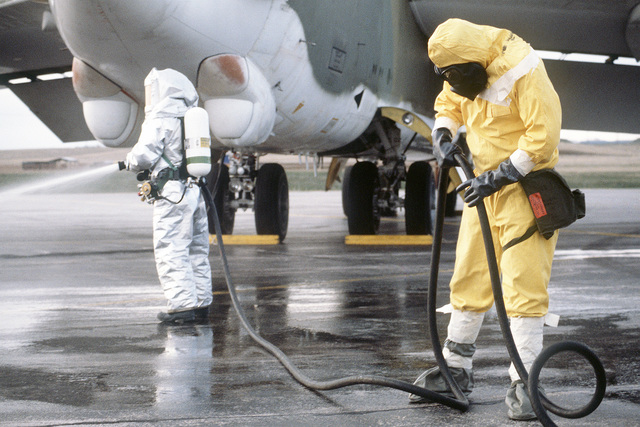 Members of the Strategic Air Command (SAC), wearing nuclear biological chemical (NBC) protective gear, participate in the decontamination of a B-52H Stratofortress aircraft during Exercise GLOBAL SHIELD '84